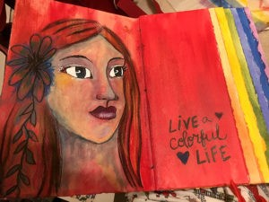 An art journal featuring a female portrait on a red background with the words live a colorful life.
